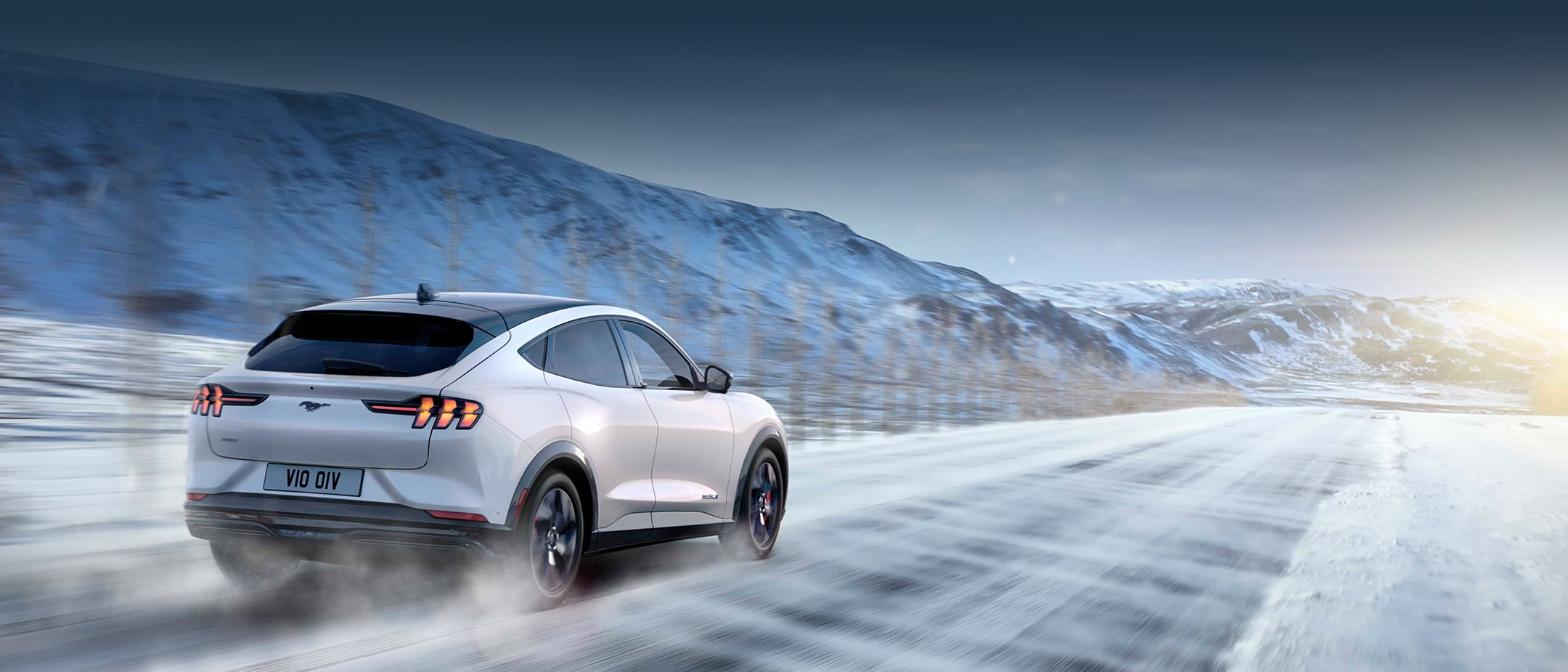 All-New Ford Mustang Mach-E in motion driving on snowy road surrounded by mountains