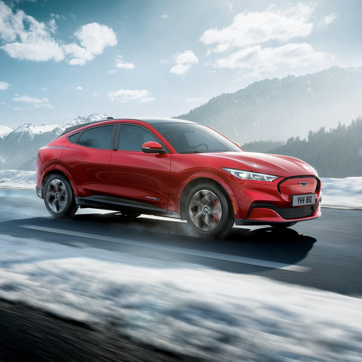 All-New Ford Mustang Mach-E driving through snowy mountains
